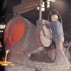 Immagine di una siviera dalla quale un operaio sta effettuando una colata
