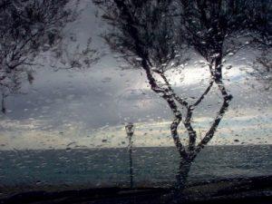 Immagine di una finestra bagnata dalla pioggia e di un paesaggio che trasuda petricore...