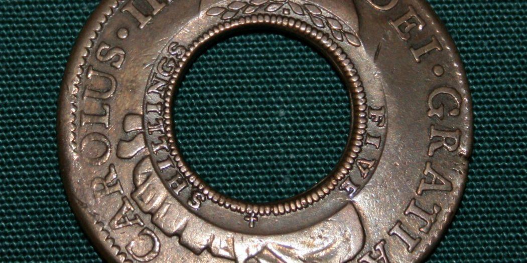 Immagine della moneta d'argento che è stata bucata al centro perché non venisse più esportata e restasse invece in circolazione